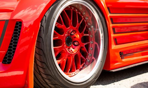 Red sports tuned car rear view of the wheel, close-up . Fashion car day on the road